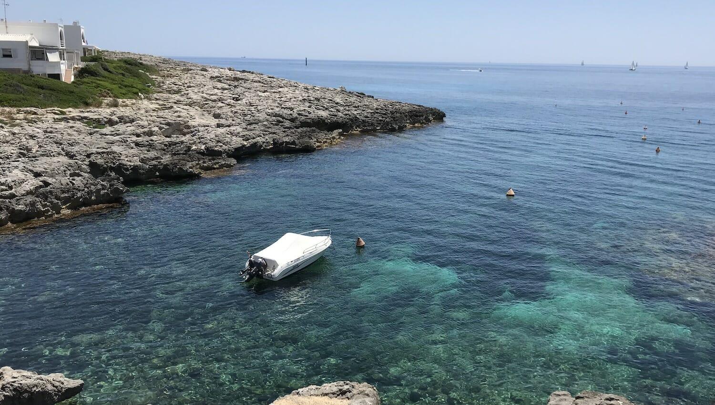 Barco amarrado en agua cristalina en la cala de Biniancolla