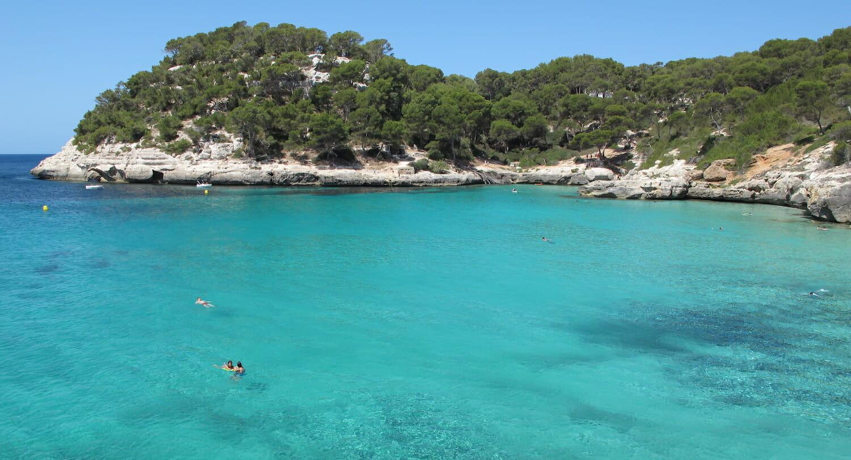 Mar turquesa con saliente de vegetación con pinos en Menorca