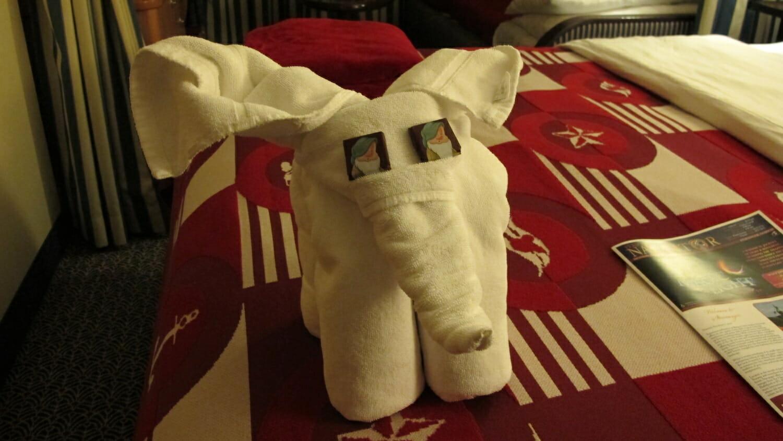 Camarote Disney con elefante de toallas sobre la cama