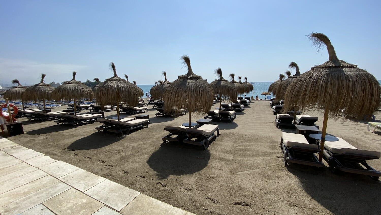 Hamacas en la arena con sombrillas de paja