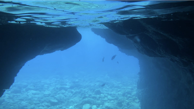 Agua turquesa bajo la superficie de la cueva En Caló Jávea