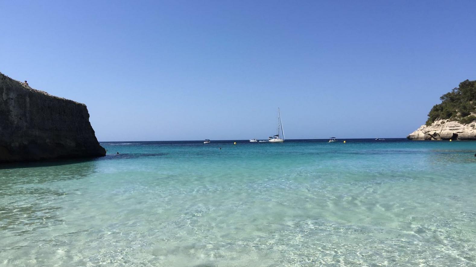 Foto de cala Mitjana en Menorca tomada desde la orilla con el agua transparente y un velero al fondo