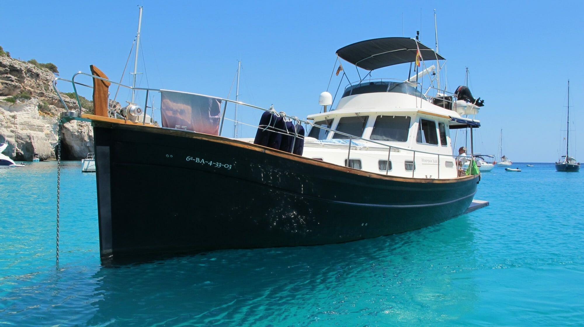 Llaüt, embarcación típica de Menorca, en una cala de mar azul