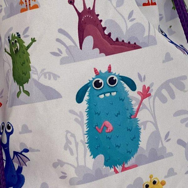 Vista con detalle de mochila saco con estampado monstruos
