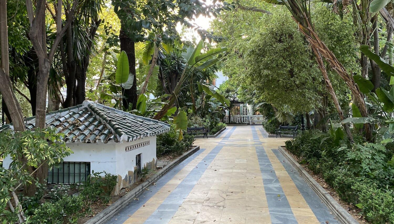 Paseo de la alameda con arboles frondosos y pequeña casita en Marbella